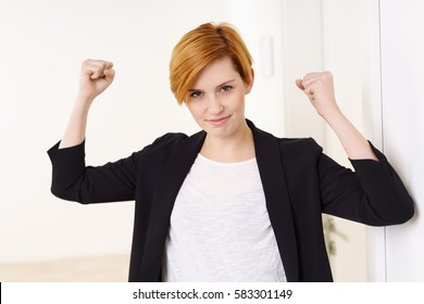 Pretty young woman with short red hair in black jacket and white shirt standing with her hands up clenching fists, confident and happy, looking at camera