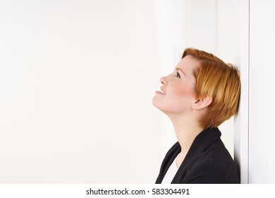 Pretty young woman with short red hair and rosy cheeks wearing black jacket, leaning back on white wall indoors and looking up. Side portrait with copy space