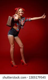 Pretty young woman in shorts,red high heels, red bandana and decolletage colorful shirt stands holding suitcase and asks for hitchhiking against red background. Full-growth retro-style pin-up portrait