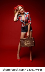Pretty young woman in shorts,red high heels, red bandana and decolletage colorful shirt stands holding suitcase and fixing her hairstyle against red background. Full-growth retro-style pin-up portrait