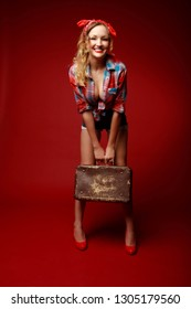 Pretty young woman in shorts,red high heels, red bandana and decolletage colorful shirt stands holding suitcase and smiling against red background. Full-growth retro-style pin-up portrait