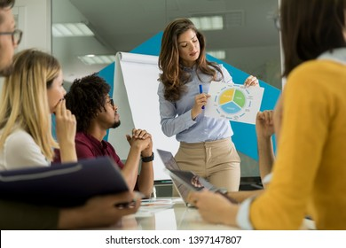 Pretty young woman showing paper chart to young workers at small startup company