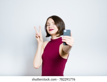 Pretty young woman showing a sign of freedom, victory with the phone, isolated on background