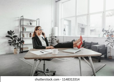 Pretty young woman sits in chair and holds legs on table. She wears black suit and red high heels. Girl talks on the phone. She is busy