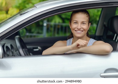 Pretty Young Woman Sitting Inside the Car, Smiling at the Camera While Leaning on the Open Window
