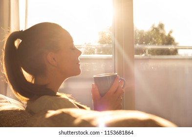 Pretty young woman sitting on sofa and enjoying first morning coffee on sunshine