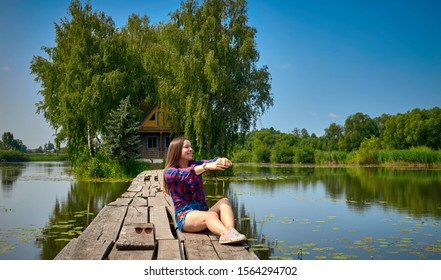 pretty young woman sitting on a wooden bridge near a wooden log house by the river