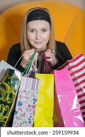 Pretty young woman sitting on the chair and holding a shopping bags. Woman on the shopping