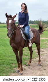 Pretty young woman sitting on a horse while riding