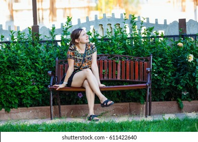 Pretty young woman sitting on a bench in the park on background of bright green foliage. Selective focus on girl.