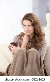 Pretty young woman sitting on sofa covered with blanket, drinking tea, smiling.?