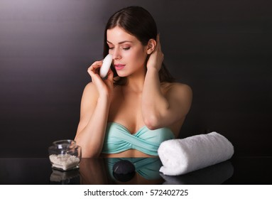 Pretty young woman with skin care products