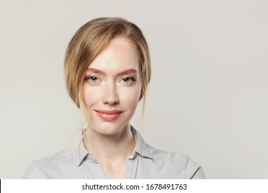 Pretty young woman smiling, female face close up on white