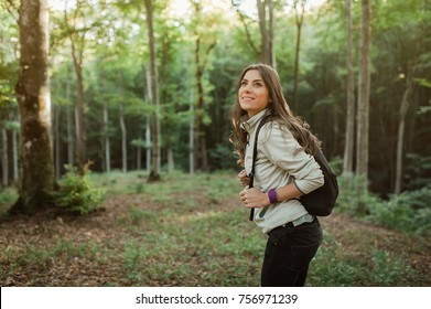 Pretty young woman smiling happy  carrying a  backpack in the forest on sunset light in the autumn season.