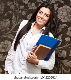 pretty young woman smiling and holding notebooks against a vintage background