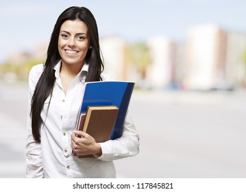 pretty young woman smiling and holding notebooks, outdoor