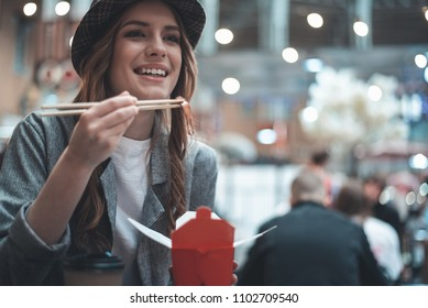 Pretty young woman is smiling while enjoying oriental dish. She is sitting at the table and holding chopsticks and take-away box in hands. There is cup of coffee near girl