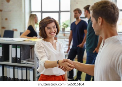 Pretty young woman smiling while greeting man with handshake, standing in office environment with other people in background soft focus