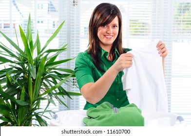 Pretty Young Woman Sorting Through The Laundry Basket