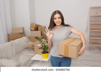 Pretty young woman standing with cardboard box in her hand showing ok with her fingers. Female in the living room ready to unpack boxes after relocating.