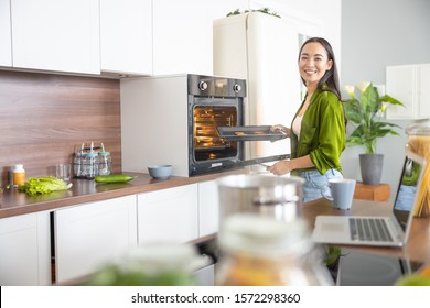 Pretty young woman standing in front of the oven
