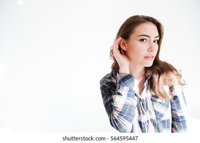 Pretty young woman standing with hand at ear to hear better isolated over white background