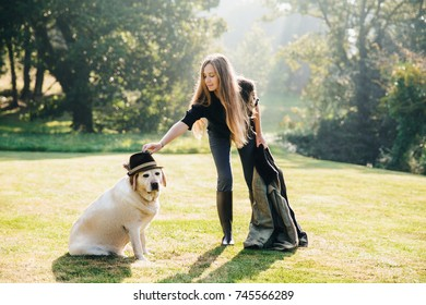 Pretty young woman standing on grass, holding parka and adjusting hat on her dog.