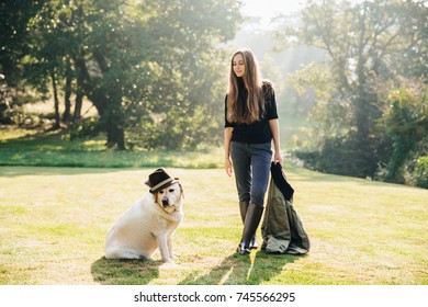 Pretty young woman standing on grass, holding parka and looking at funny dog in hat.