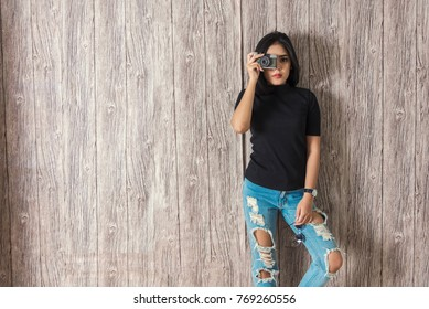 Pretty young woman standing on wall with take a photo. Vintage and retro filtered. Backdrop for design art work. Picture for add text message.