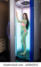 Pretty young woman standing in solarium at the hotel spa