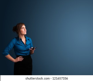 Pretty young woman standing and typing on her phone with copy space