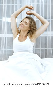Pretty young woman stretching on the bed