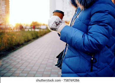 Pretty young woman in stylish blue down jacket with fur hood holding cup in hands. Warm soft cozy image. Details. Drinking take away coffee. Breakfast on the go. Instagram style toned image
