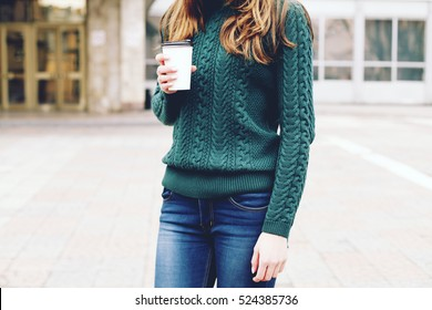 Pretty young woman in stylish green sweater holding cup in hands. Warm soft cozy image. Details. Drinking take away coffee. Breakfast on the go. Instagram style toned image