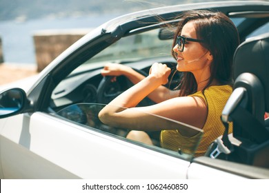 Pretty young woman with sunglasses driving in white cabriolet car