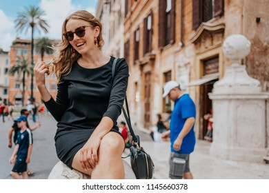Pretty young woman with sunglasses smiling in a short black dress while on a vacation