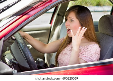 Pretty young woman with surprised face driving her new red car