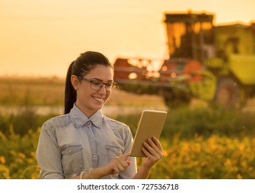 Pretty young woman with tablet standing in soybean field with combine harvester working in background