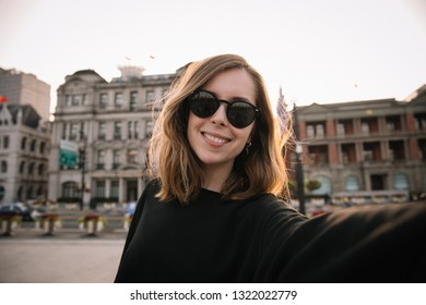 Pretty young woman taking selfie for social media while travel in Shanghai, China