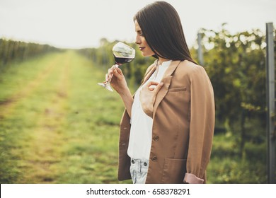 Pretty young woman tasting red wine in the vineyard