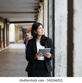 Pretty young woman thinking and holding a tablet