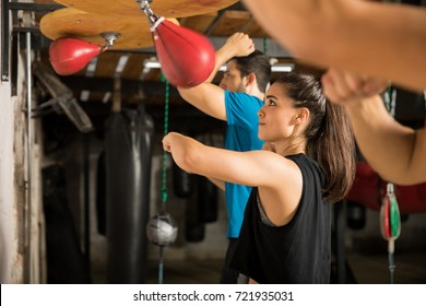 Pretty young woman training with a speed bag with a group of people in a boxing gym