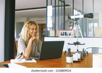 Pretty young woman using laptop computer. Telescope standing on the table