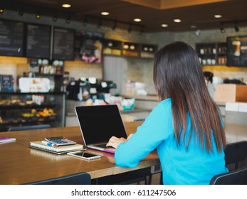 Pretty Young woman using laptop computer. Female working on laptop in an indoor cafe.