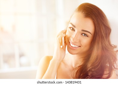 pretty young woman using mobile phone at home