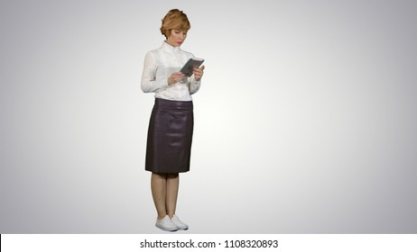 Pretty young woman using tablet on white background