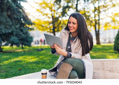 Pretty young woman using tablet at public park