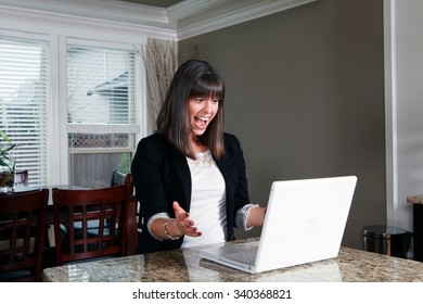 A pretty young woman very happily smiling at her laptop computer.
