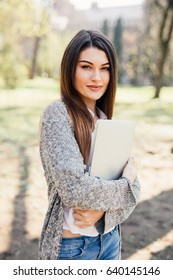 Pretty young woman walking with laptop under the hand.