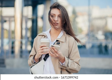 Pretty young woman walking at the street, holding mobile phone, drinking coffee